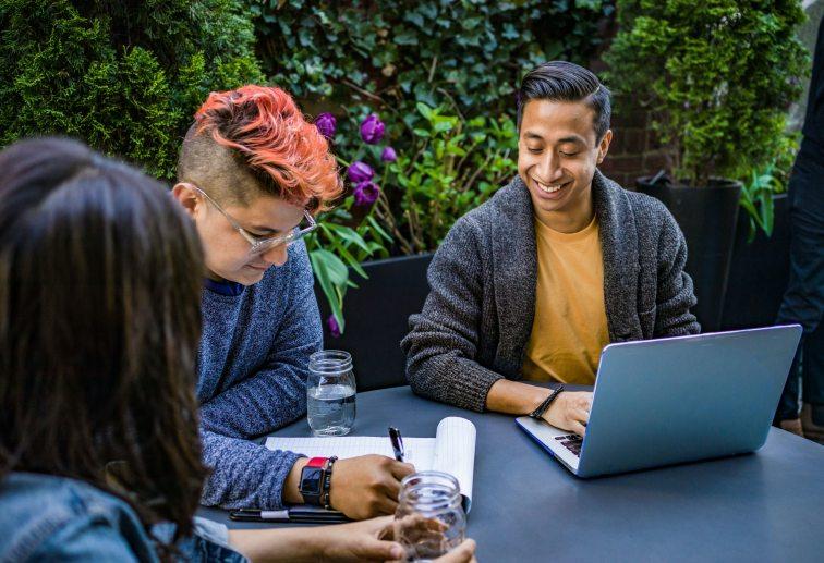 man-in-orange-crew-neck-shirt-using-laptop-beside-two-people-2422281